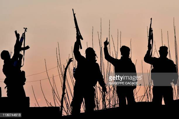 TOPSHOT USbacked Syrian Democratic Forces fighters celebrate after fighting Islamic State group jihadists near the village of Baghouz in the eastern...