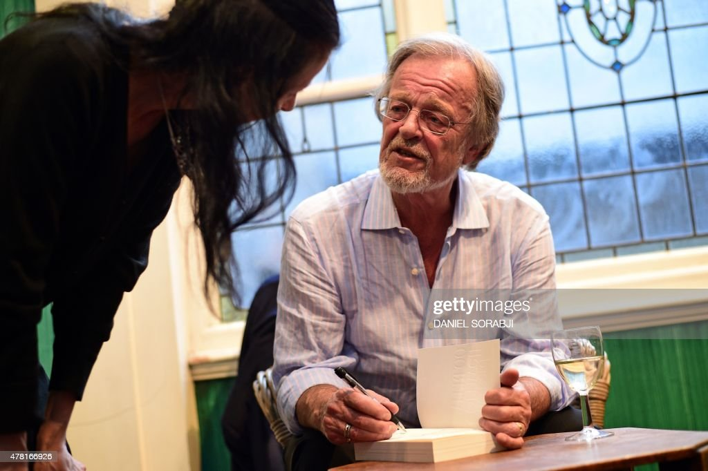 US-based British author Bernard Cornwell signs a copy of his first book of non-fiction 'Waterloo: The History of Four Days, Three Armies and Three Battles' for a fan after giving a talk at a bookshop in London on June 16, 2015. Cornwell, best known for his popular historical novels featuring the adventures of the Richard Sharpe, an British soldier in the Napoleonic Wars, is the author of over 50 novels and one work of non-fiction, 'Waterloo'.