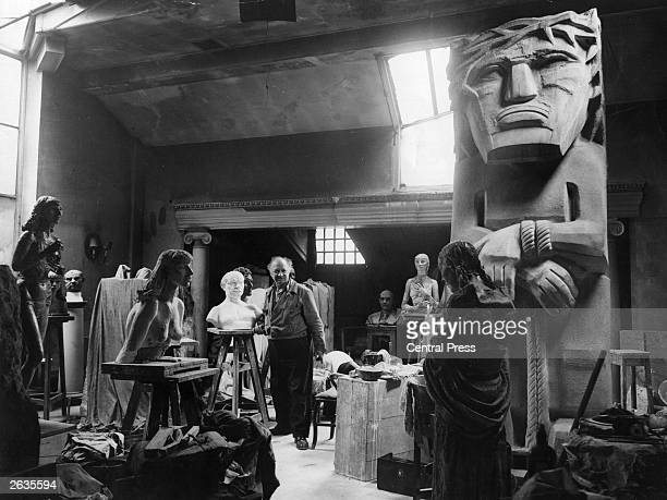 USborn British sculptor Jacob Epstein in his studio at Hyde Park Gate London surrounded by his works The large sculpture on the right is 'Behold The...