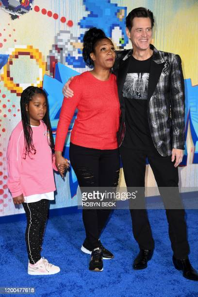 USCanadian actor Jim Carrey poses with US actress Tiffany Haddish and her god daughter Cadence Martin as they arrive to attend a special screening of...