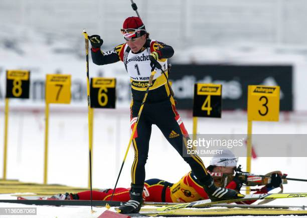 Uschi Disl of Germany leaves the shooting area and Liv Grete Poiree of Norway still shoots in the background during the women's 10 km pursuit during...