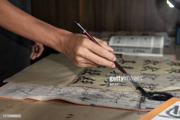 use a brush at home to dip your elbows in ink to write calligraphy - escritura japonesa fotografías e imágenes de stock