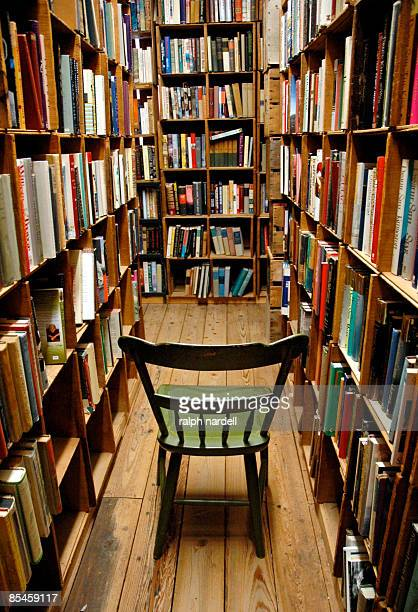 Used bookstore and empty chair amid bookshelves