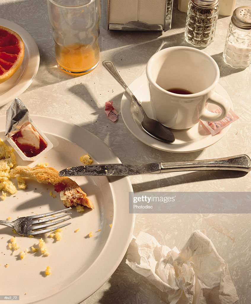used breakfast dished and silverware such as knives and cups clutter a table : Foto de stock