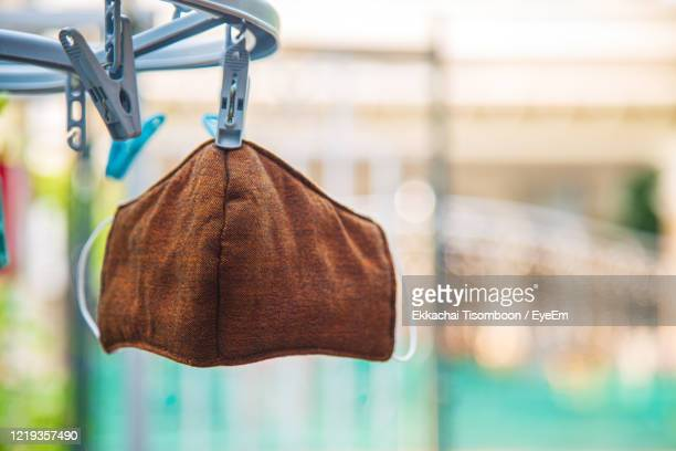 a used brown flu mask hanging with plastic clothespin under sunlight after wash - masque tissus photos et images de collection