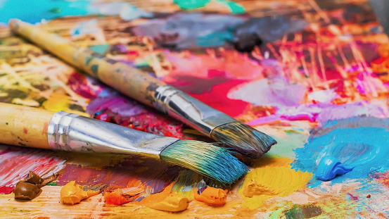 Used brushes on an artist's palette of colorful oil paint 636761588