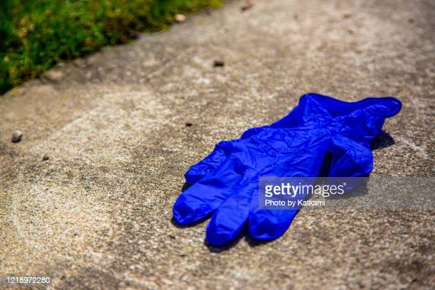 used glove on pavement - surgical glove stock pictures, royalty-free photos & images