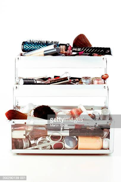 Used make-up and brushes in trays of opened vanity case, close-up