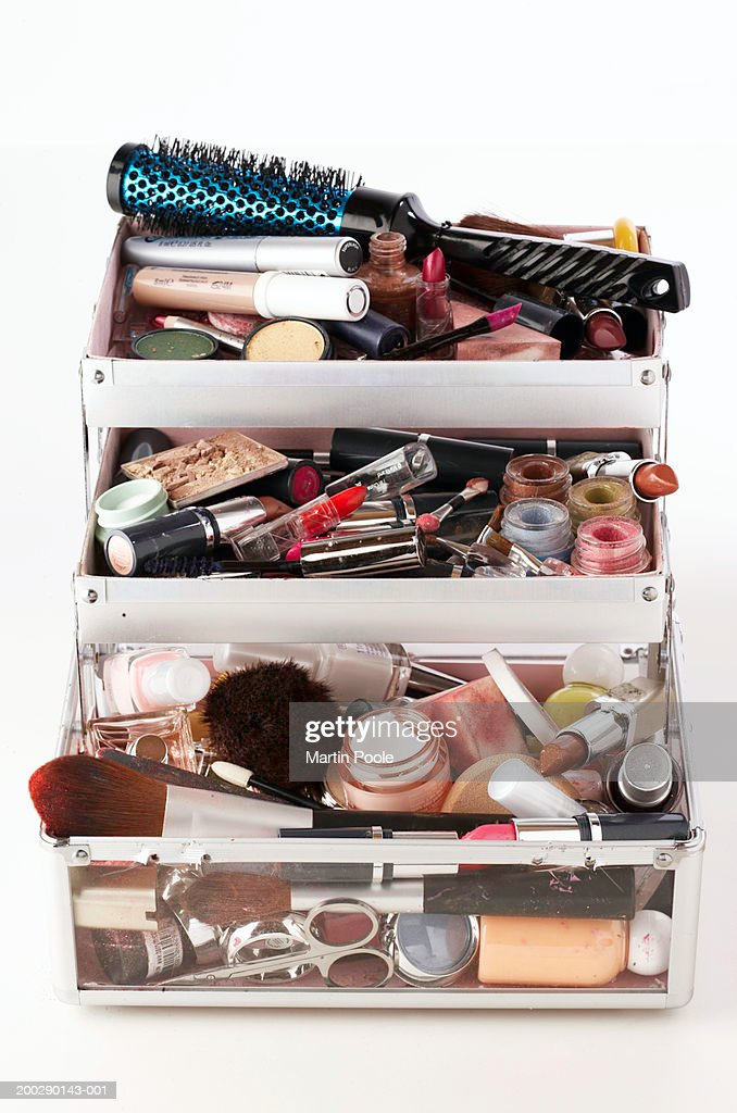 Used make-up and brushes in trays of opened vanity case, close-up : Stock Photo