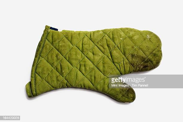 used oven mitt. a quilted padded fabric, green, heat resistant mitt.  - green glove stock photos and pictures
