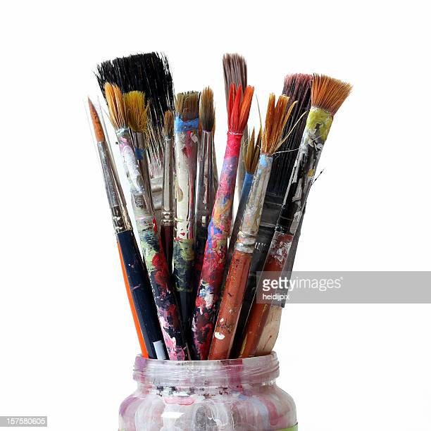 Used paintbrushes of various sizes in a jar