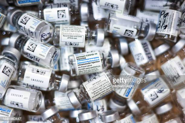 Used vials of the Johnson & Johnson COVID-19 vaccine, the newest vaccine approved by the U.S. FDA for emergency use, sit in a box at an event put on...