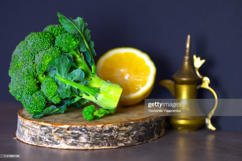 Useful foods are on the table, broccoli on a wooden stand and sliced lemon. : Stock Photo
