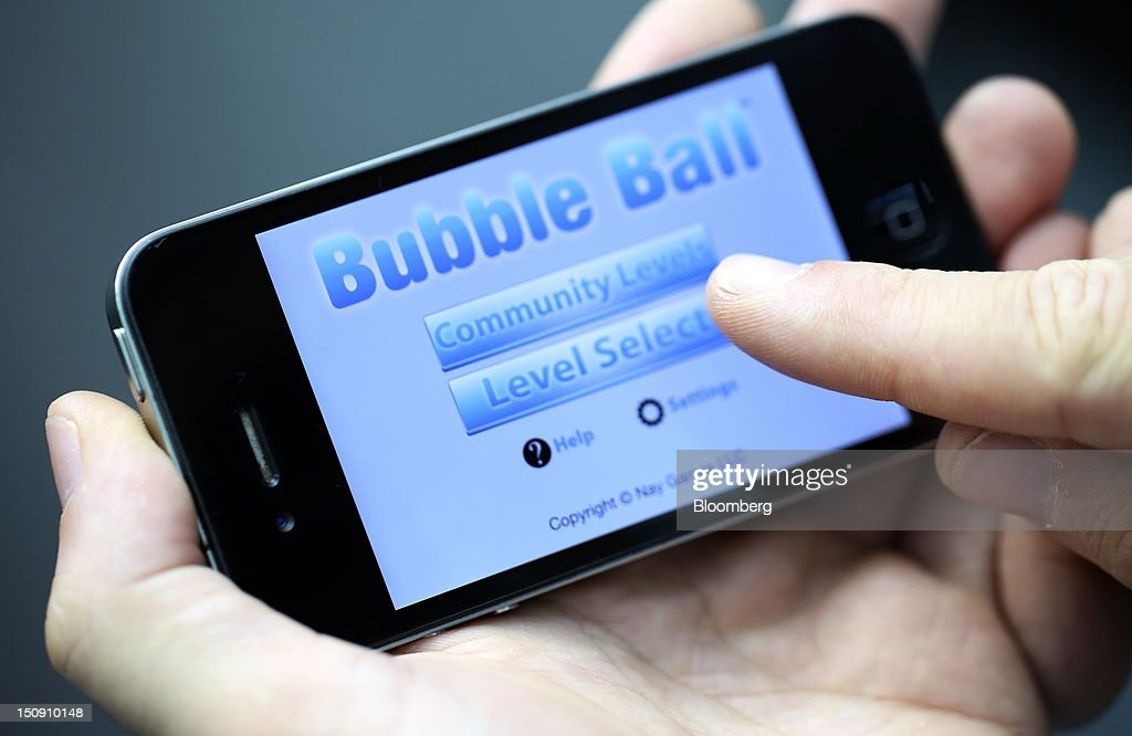 A user plays on the game Bubble Ball, developed on the Corona social development kit, on an Apple Inc. iPhone 4 smartphone in this arranged photograph in London, U.K., on Wednesday, Aug. 29, 2012. The game, which requires players to use simple physics principles to get a ball into a goal, has been downloaded more than 15 million times and some weeks has ranked higher than 'Angry Birds' on Apple's App Store. Photographer: Chris Ratcliffe/Bloomberg via Getty Images