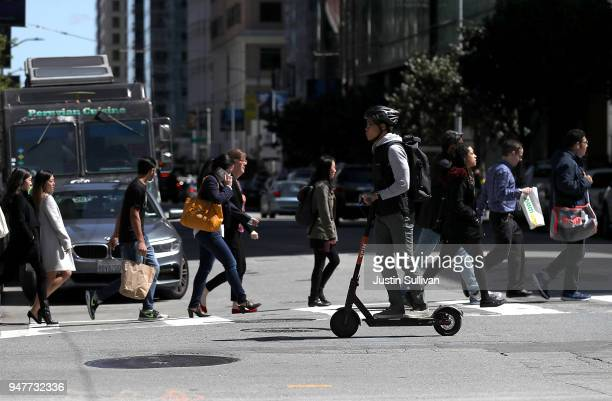 A user rides a Spin scooter on April 17 2018 in San Francisco California Three weeks after three companies started placing electric scooters on the...