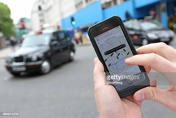 A user scans for an available vehicle using the Uber Technologies Inc's app on an Apple Inc iPhone 5 smartphone in this arranged photograph in London...