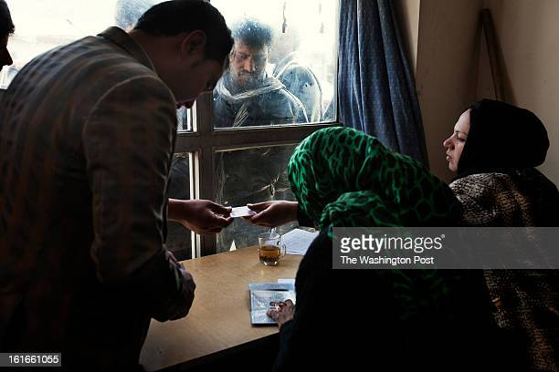 KABUL AFGHANISTAN – JANUARY Users and employees of the traffic department in Kabul process the paperwork to renew driving licenses while a long queue...