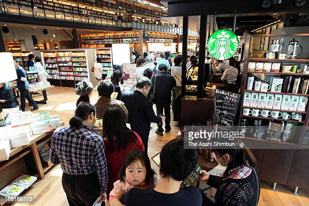 Users queue at a coffee shop Starbucks opens at the renovated Takeo City Library during a preview on March 31 2013 in Takeo Saga Japan The city...