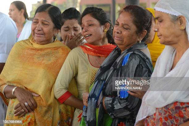 Usha and Babby along with relatives cry as they stand next to the burning pyre of their brother Tilak Raj who was killed when a train ploughed into a...