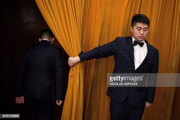 A usher opens a curtain to a security officer during the second plenary session of the National People's Congress China's legislature at the Great...