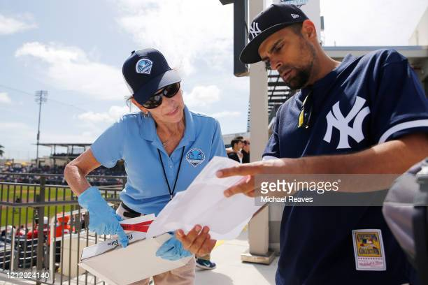 Usher, wearing protective gloves, helps a fan find their seat prior to a Grapefruit League spring training game between the Washington Nationals and...