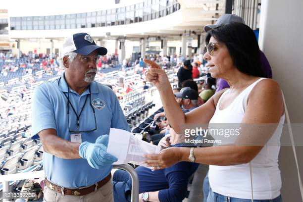 A usher wearing protective gloves helps a fan find their seat prior to a Grapefruit League spring training game between the Washington Nationals and...