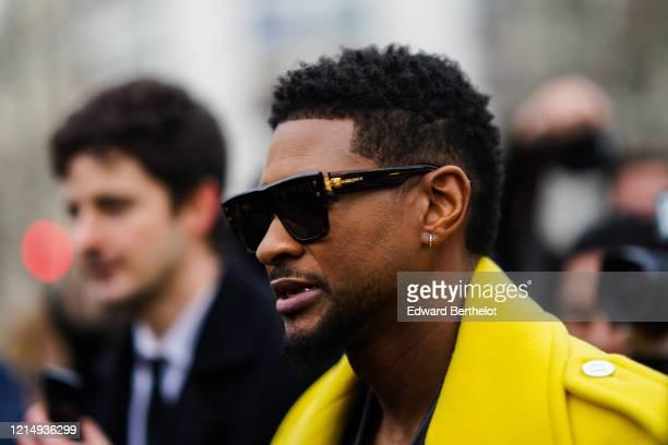 Usher wears Balmain sunglasses, earrings, a yellow coat, outside Balmain, during Paris Fashion Week - Womenswear Fall/Winter 2020/2021, on February...