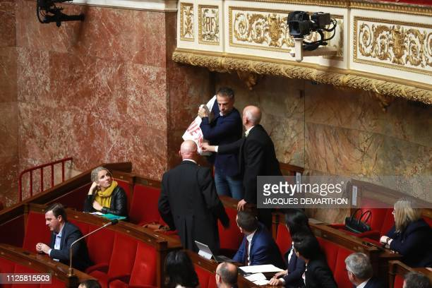 Ushers try to grab a banner that reads, 'France kills in Yemen' being held by French lawmaker in the National Assembly Sebastien Nadot, during a...