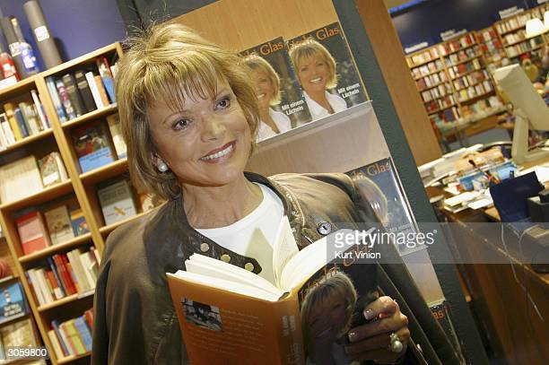 "Ushi Glas poses with a copy of her new book ""Mit Einem Lacheln"" at the Thalia bookstore in Berlin on March 9, 2004. The book details her life,..."