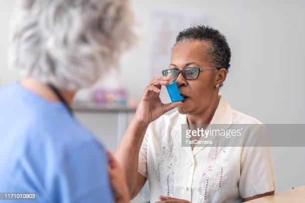 using a asthma inhaler - bomba para asma imagens e fotografias de stock