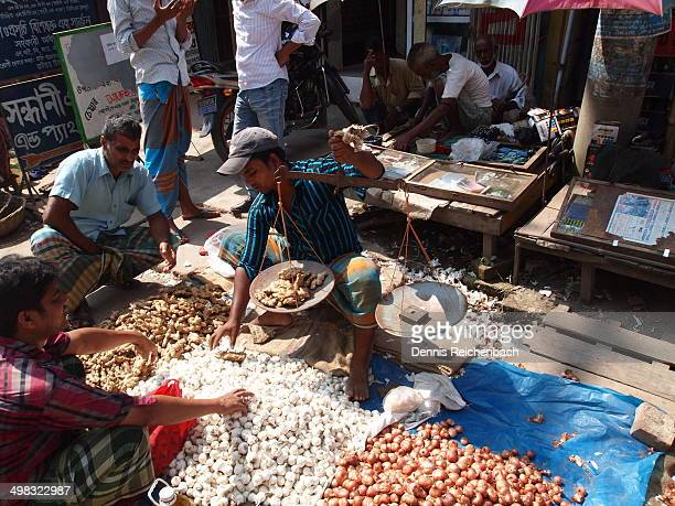 Using a balance to weigh out ginger for sale in this street market.