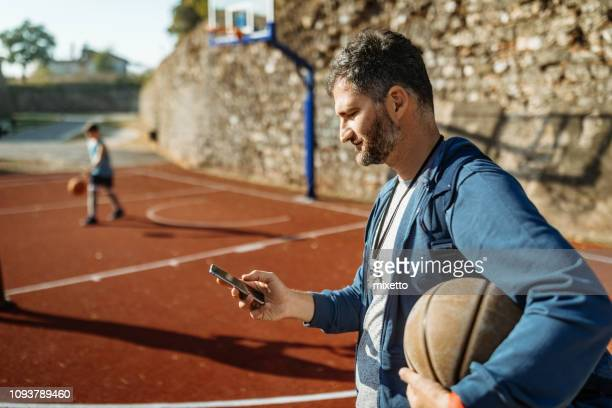 using a mobile phone in a sport - checking sports stock pictures, royalty-free photos & images