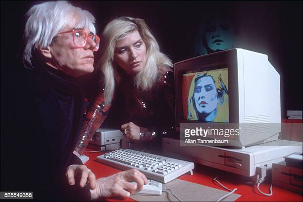 Using a photograph he took of Debbie Harry for digital manipulation Andy Warhol demonstrates the new Amiga Computer at Lincoln Center New York New...