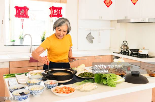 using a recipe on a tablet for chinese new year meal - chinese decoration stock pictures, royalty-free photos & images