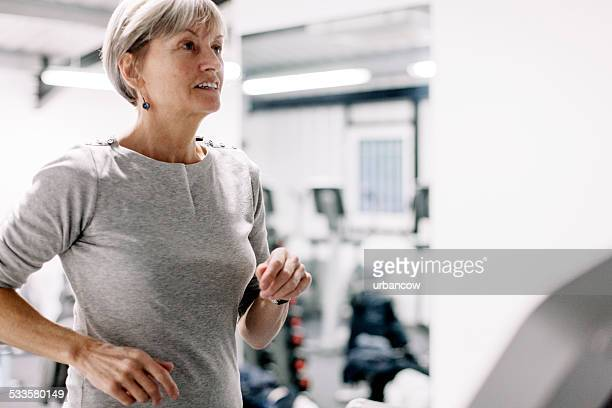 Using a running machine; beautiful, senior woman