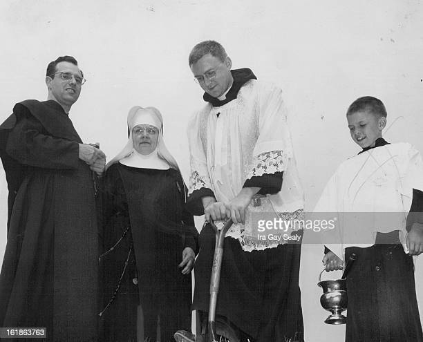 JUL 14 1954 Using a shovel presented by first grade students at Mount Carmel grade school Father Francis Brown breaks ground at site of new $120000...