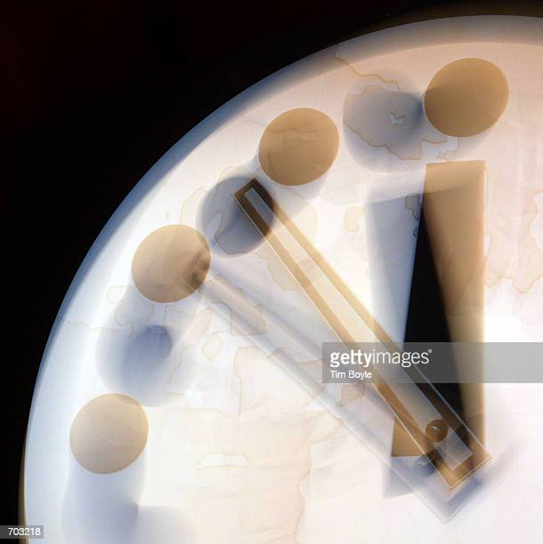 Using a slow camera exposure to simulate clock movement the hands of the Bulletin of the Atomic Scientists Doomsday Clock are seen at 1153 pm two...