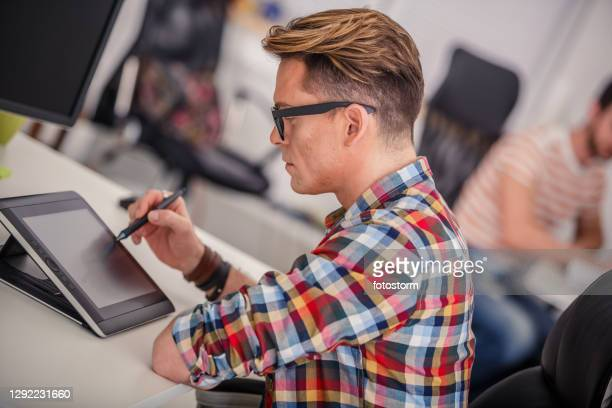 using a tablet device to expedite on pressing tasks at the workplace - animator stock pictures, royalty-free photos & images