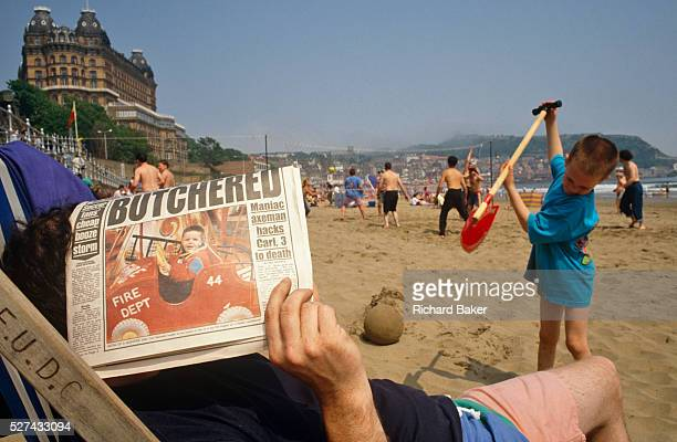 Using a tabloid newspaper a father seeks shelter from sunshine while sitting in a council deck chair On the front page of the paper is a headline...