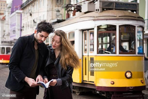 Com um livro de Guia de viagem numa cidade europeia