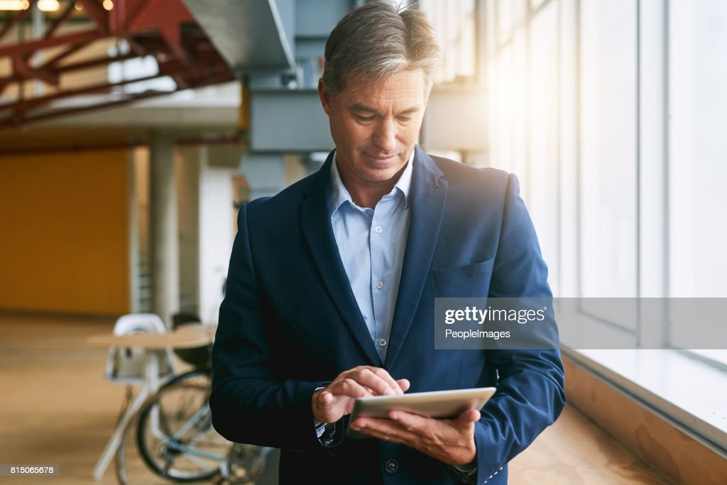 Using all the latest apps to help manage his business : Stock Photo