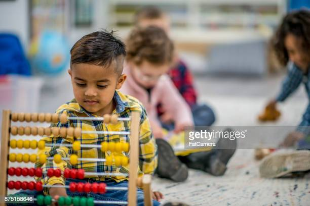 using an abacus - migrant children stock photos and pictures