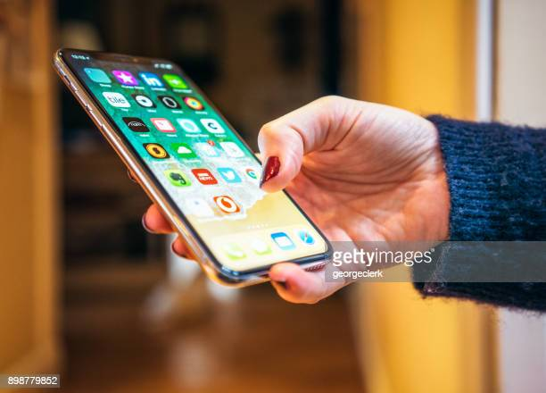 using an iphone x at home - home icon stock photos and pictures