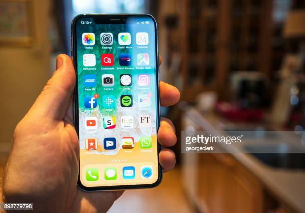 using an iphone x in the kitchen - home icon stock photos and pictures