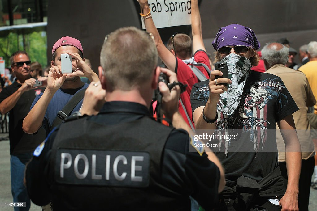 Using cameras a police officer squares off with protestors during a demonstration organized by National Nurses United in Daley Plaza where they were calling for a 'Robin Hood' tax on stocks, bonds, derivatives and other financial instruments May 18, 2012 in Chicago, Illinois. This was the fifth day of protests in what is expected to be a full week of demonstrations as the city prepares to host the NATO Summit May 20-21.