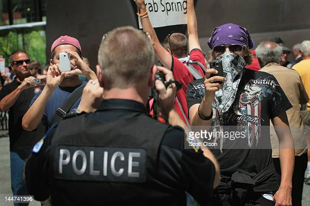 Using cameras a police officer squares off with protestors during a demonstration organized by National Nurses United in Daley Plaza where they were...