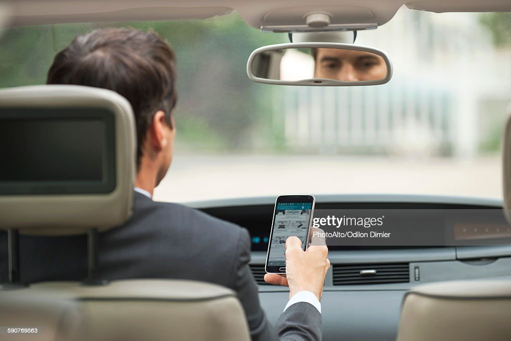 Using cell phone while driving car : Stock Photo