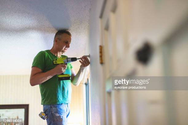 using cordless power drill mature adult male working on home remodel project photo series - selective focus stock pictures, royalty-free photos & images