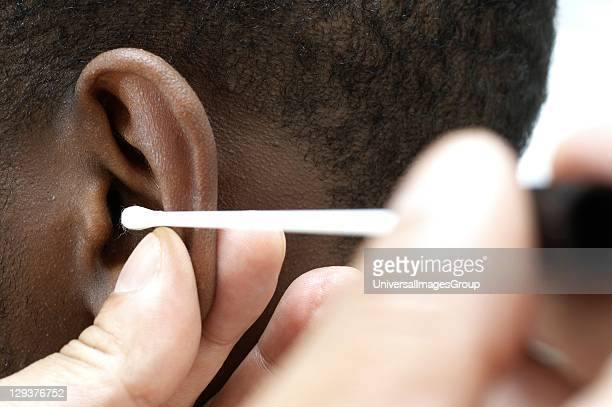 GP using cotton bud to clean ear canal of young male patient