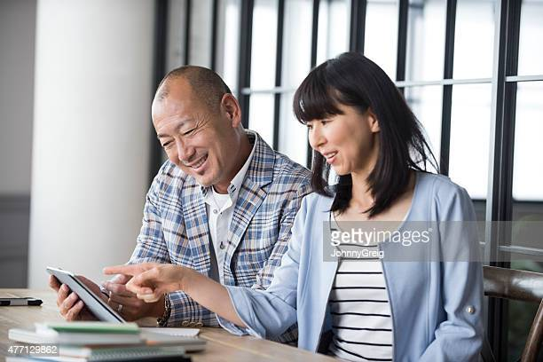 using digital tablet - mid adult couple stock pictures, royalty-free photos & images